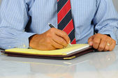 Businessman writing in note pad — Stockfoto