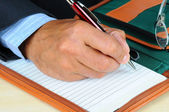 Businessman writing in note pad — Stock Photo