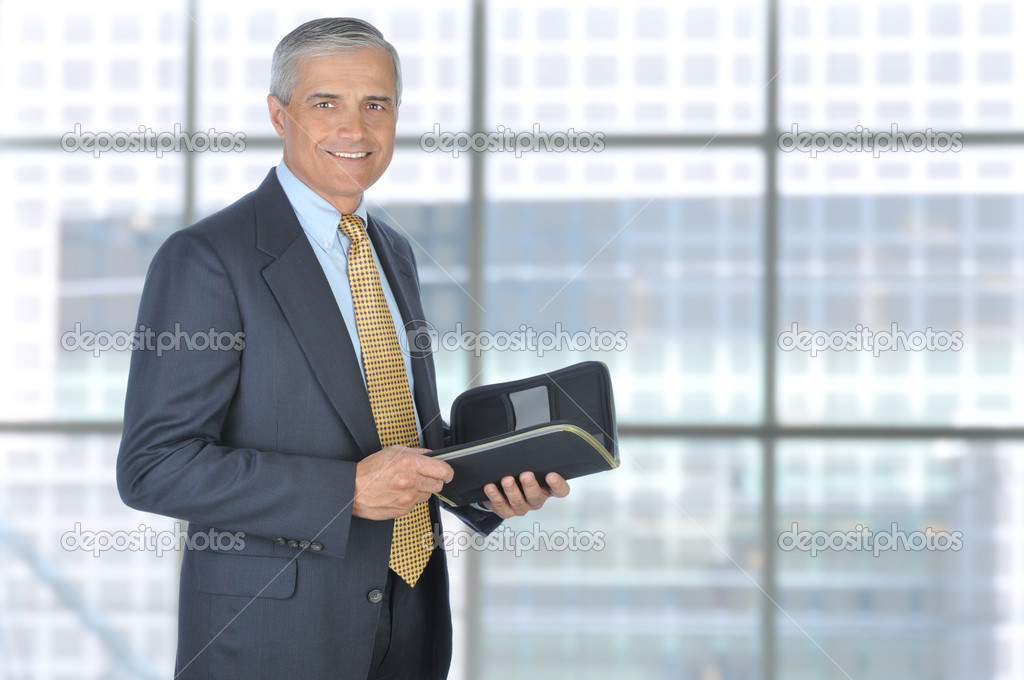 Standing Middle Aged Businessman with Planner Notebook in Modern Office Setting, Horizontal Format. — Stock Photo #4707872