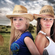 Stock Photo: Two Girls Wearing cowboy Hats And Smiling