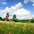 Stock Photo: Happy girl jumping on a Green field