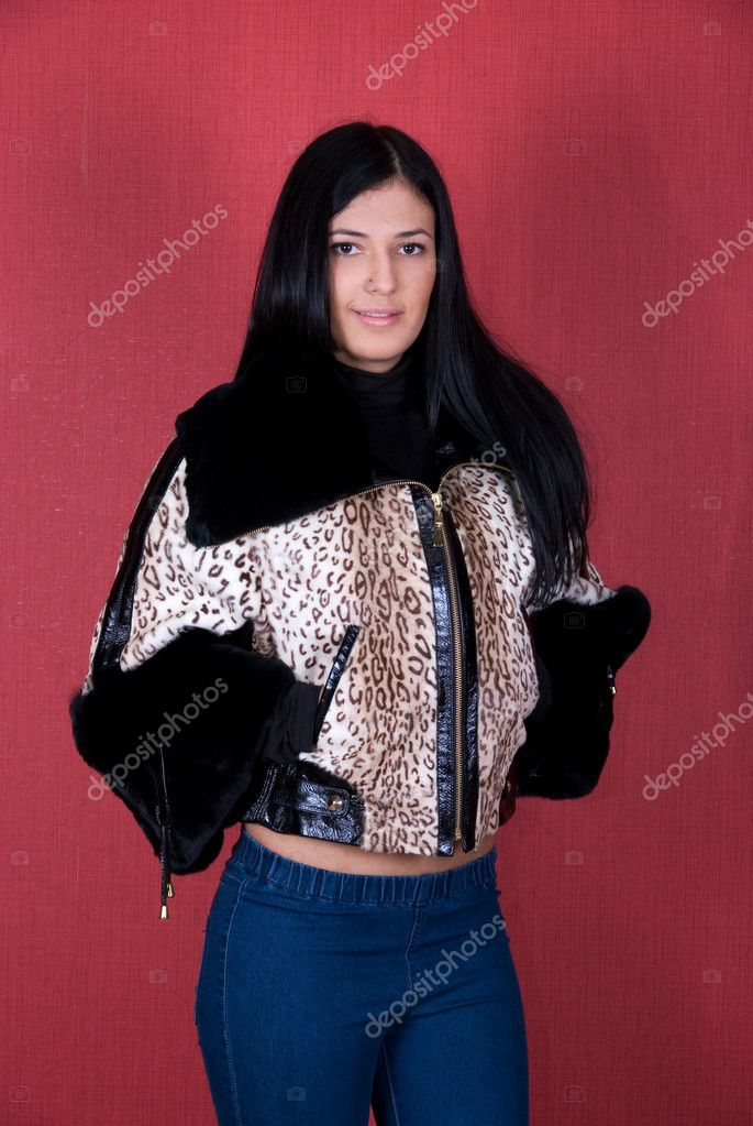 Beautiful woman in a leopard jacket on a red background  Stock Photo #5060611