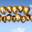 Gold Happy Birthday balloons in the sky — Stock Photo #4914126