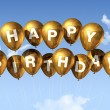 Gold Happy Birthday balloons in the sky — Stock Photo