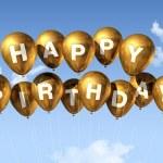 Gold Happy Birthday balloons in the sky — Stock Photo