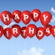 Red Happy Birthday balloons in the sky — Stock Photo #4914139