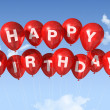 Red Happy Birthday balloons in the sky — Stock Photo