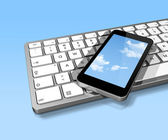 Mobile phone on a computer keyboard — Stock Photo