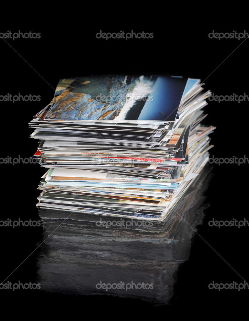 A Stack of 4x6 inch (10x15cm) photos on black reflecting surface. The image on the top of the pile (c) by the photographer of the whole image  Stock Photo #4352421