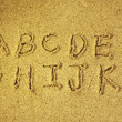 Alphabet letters handwritten in sand on beach — Stock Photo #4125217