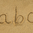 Alphabet letters handwritten in sand on beach — Foto de Stock