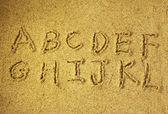Буквы алфавита, от руки в песок на beach — Стоковое фото
