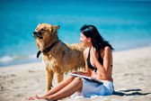 Beautiful young woman and dog on the beach — Stock Photo