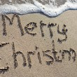 Stock Photo: Merry Christmas written on sand