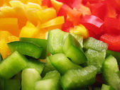 Yellow, red and green peppers Bulgarian. Slicing. Cubes — Stock Photo