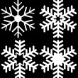 Vecteur: Set of Four Snowflakes Isolated on Black