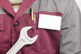 Name tag on uniform and wrench — Stock Photo