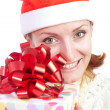 Happy smiling woman in christmas hat with gift — Stock Photo