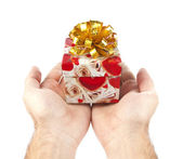 Small red gift in palms of hands — Stock Photo