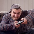Man with joystick playing video games - Stock Photo