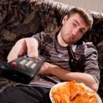 Сонный человек смотрит телевизор — Стоковое фото