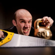 Man with saw and heavy weight of gold — Stock Photo