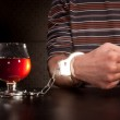 Hand locked to glass of alcohol — Stock Photo
