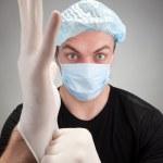 Dark surgeon wearing gloves — Stock Photo