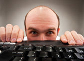 Timid nerd hiding under computer keyboard — Stock Photo