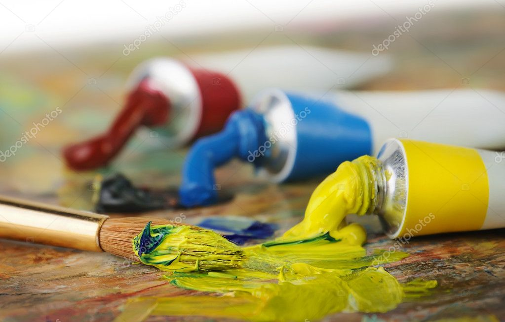 Oil paint tubes and painbrush over colorful artist's palette — Stock Photo #4336161