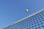 Yellow Tennis Ball Flying Over the Net — Stock Photo
