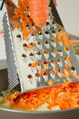 Chef grating carrot — Stock Photo