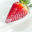 Strawberry splashing into milk — Stock Photo #5366010