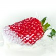 Strawberry splashing into milk — Stock Photo