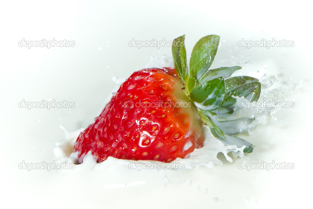Delicious fresh strawberry falling into splashing milk — Stock Photo #5366375