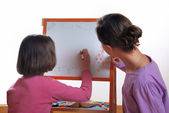 Youngs girls drawing on the white board — Stock Photo