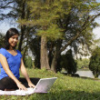 Woman with laptop at park — Stockfoto