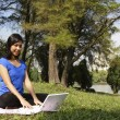 Woman with laptop at park — Stock fotografie