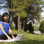 donna con il portatile al parco — Foto Stock