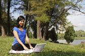 Woman with laptop at park — Stock Photo