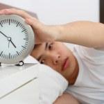 Sleepy man with clock — Stock Photo
