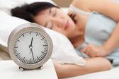 Clock and sleeping woman — Stock Photo