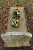 Tombstone covered with flowers — Stock Photo