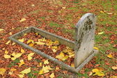 Vieja piedra sepulcral y hojas de otoño — Foto de Stock