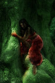 The fantastic girl on a green tree trunk — Stock Photo