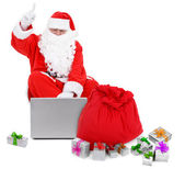 Surprised Santa claus with laptop and presents — Stock Photo