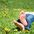 Feet of a  young woman lying in a meadow — Stock fotografie