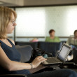 Woman in Airport Using Netbook — Stock Photo