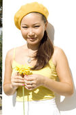 Closeup portrait of a girl with yellow flower — Stock Photo