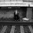 Stock Photo: Thoughtful girl sitting near railroad